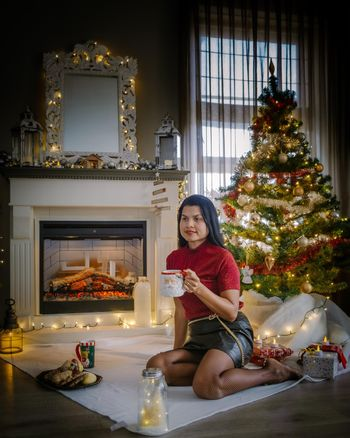 Cute, young Asian mid age woman by fireplace with a Christmas tree,Family sitting on a floor. Girlnear christmas tree with candle lights