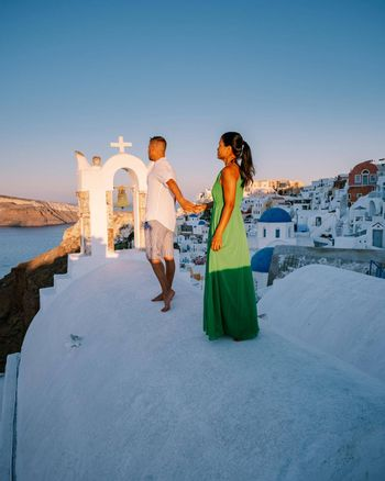 Santorini Greece, young couple on luxury vacation at the Island of Santorini watching sunrise by the blue dome church and whitewashed village of Oia Santorini Greece during sunrise during summer vacation, men and woman on holiday in Greece