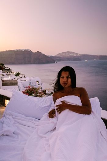 Santorini Greece, young woman on luxury vacation at the Island of Santorini watching sunrise by the blue dome church and whitewashed village of Oia Santorini Greece during sunrise during summer vacation, men and woman on holiday in Greece
