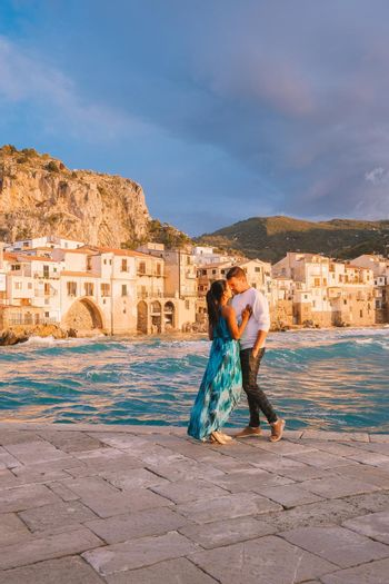 Cefalu Sicily, a couple watching the sunset at the beach of Cefalu Sicilia Italy, mid-age men and woman on vacation Sicily.