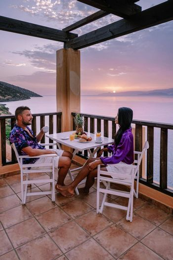 table and chairs with breakfast during sunrise at the meditarian sea in Greece. Couple having breakfast on balcony looking out over the ocean