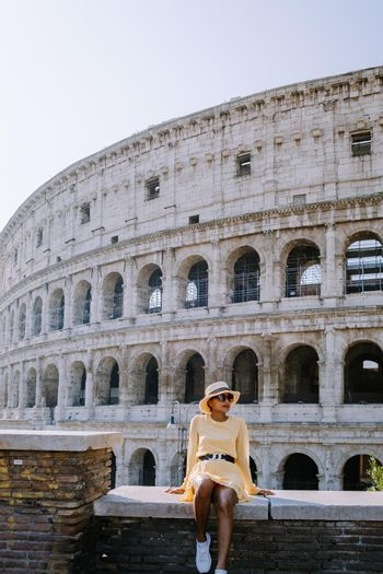 View of Colosseum in Rome and morning sun, Italy, Europe. Young woman on city trip Rome