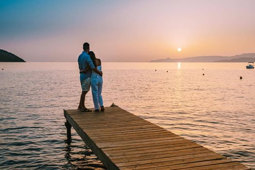 young romantic couple in love is sitting and hugging on wooden pier at the beach in sunrise time with golden sky. Vacation and travel concept. Romantic young couple dating at seaside. Crete Greece
