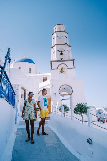 couple drinking coffee at traditional village Pyrgos Santorini Greece, young couple on luxury vacation at the Island of Santorini watching sunrise by the blue dome church and whitewashed village of Oia Santorini Greece . Europe
