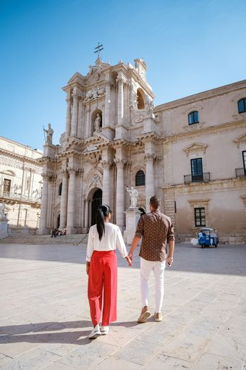 couple men and woman on citytrip Ortigia in Syracuse in the Morning. Travel Photography from Syracuse, Italy on the island of Sicily. Cathedral Plaza and market with people whear face protection during the 2020 pandemic