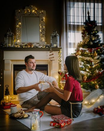 Cute, young couple by fireplace with a Christmas tree,Family sitting on a floor. Couple near christmas tree with candle lights