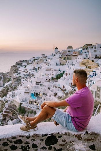 young men watching sunset,Santorini Greece, young couple on luxury vacation at the Island of Santorini watching sunrise by the blue dome church and whitewashed village of Oia Santorini Greece . Europe