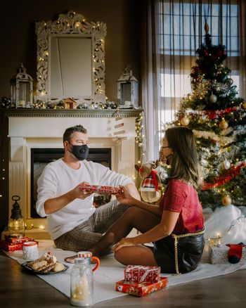 Christmas couple wearing mask during Christmas night,Close up portrait of happy mixed-races couple with christmas presents and wearing medical masks in quarantine. couple with face mask during covid outbreak pandemic