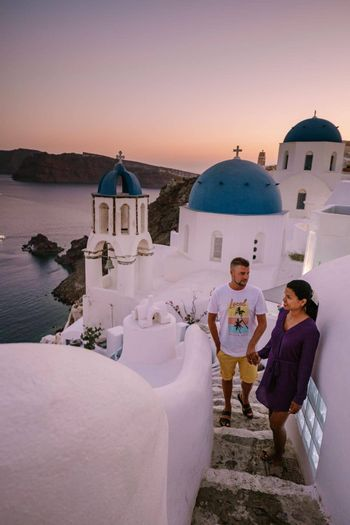 Santorini Greece, young couple on luxury vacation at the Island of Santorini watching sunrise by the blue dome church and whitewashed village of Oia Santorini Greece during sunrise during summer vacation