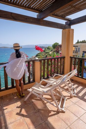 woman on balcony on holiday luxury vacation looking out over the ocean of Crete Greece Europe
