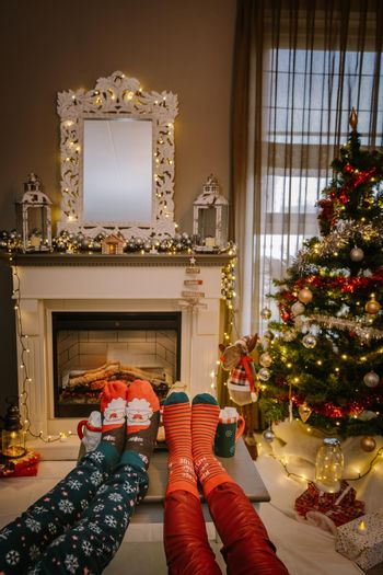 Christmas tree and fireplace, Christmas socks and hot chocolate cups by fireplace during Christmas holiday