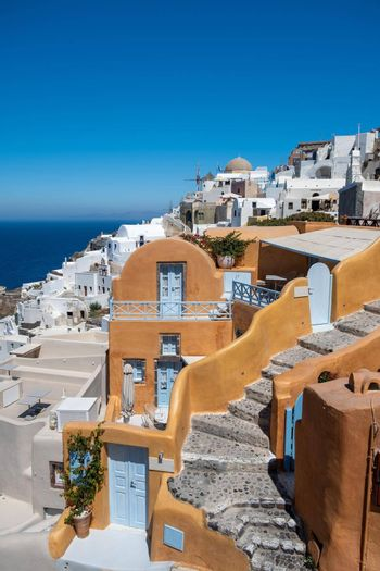 Santorini, Greece. Picturesq view of traditional cycladic Santorini houses on small street with flowers in foreground. Location: Oia village, Santorini, Greece. Vacations background Europe