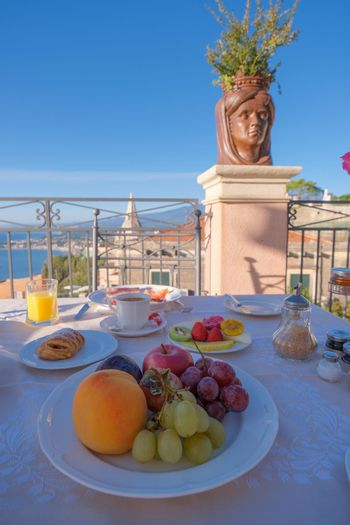 Taormina Sicily Italy breakfast table with a rooftop view over Taormina breakfast with coffee bread and fruit