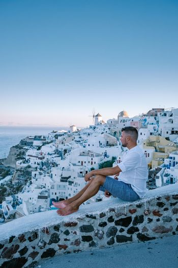 Sunset at the Island Of Santorini Greece, beautiful whitewashed village Oia with church and windmill during sunset, streets of Oia Santorini during summer vacation at the Greek Island, young men on luxury vacation Santorini
