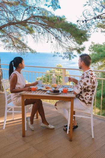 couple having breakfast in the garden looking out over the hills of Sicily, men and woman of mid-age on vacation having breakfast outside