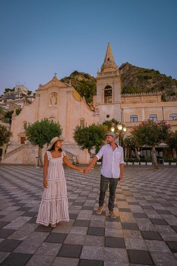 Taormina Sicily, Belvedere of Taormina and San Giuseppe church on the square Piazza IX Aprile in Taormina. Sicily, Italy. Couple on vacation at the Italian Island Sicily