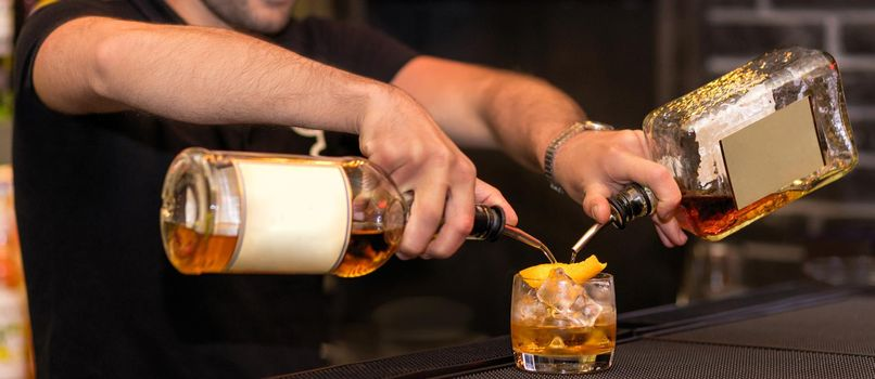 Barman making a new alcoholic cocktail, pouring drinks into a glass