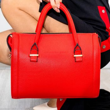 Woman holding beautiful red bag close up