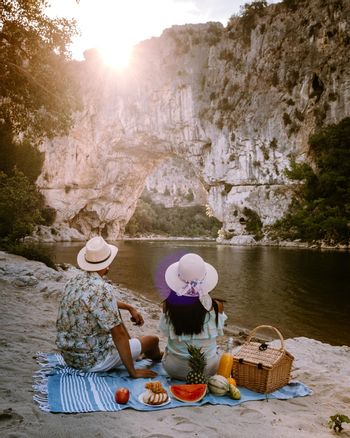 couple on the beach by the river in the Ardeche France Pont d Arc, Ardeche France,view of Narural arch in Vallon Pont D'arc in Ardeche canyon in France Europe