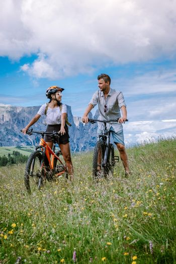 couple men and woman on vacation in the Dolomites Italy,Alpe di Siusi, men and woman on mountanbike - Seiser Alm with Sassolungo - Langkofel mountain group in background at sunset.
