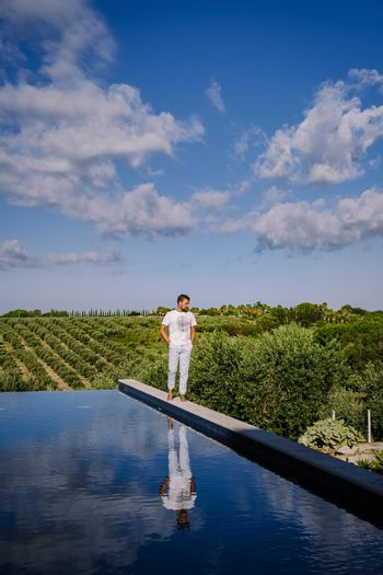 Luxury resort with a view over the wine field in Selinunte Sicily Italy. infinity pool with a view over wine fields in Sicilia men on vacation luxury hotel
