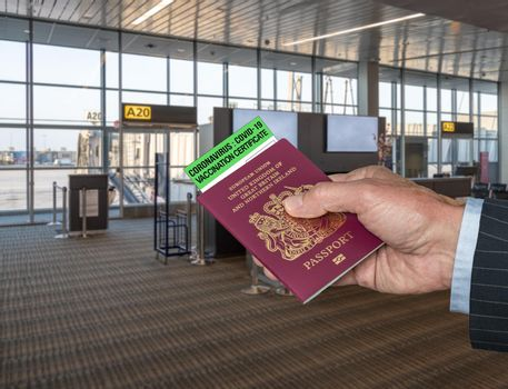 Concept of Covid-19 immune certificate and UK passport to show vaccination for virus at airport
