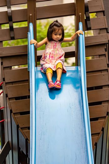 Pretty asian little girls while sliding in a playground