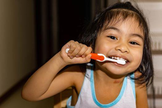 Little asian girl kid while brushing her teeth. Child while enjoying brushing her teeth