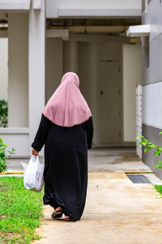 Old female muslim back shot while walking on a street