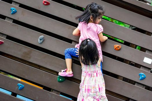 Pretty asian little twins girls while climbing in a playground and helping each other