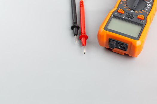 close-up view of digital electrical multimeter with probe tips on gray background