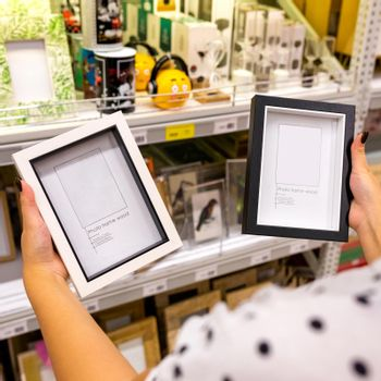 Woman holding black and white photo frames at the store