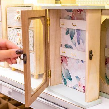 Woman opening wooden key hanger box