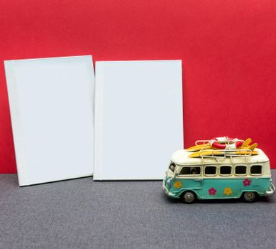 White postcard book with a car with a red background