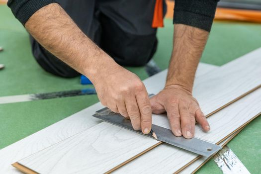 Worker measure length of the white wood laminate