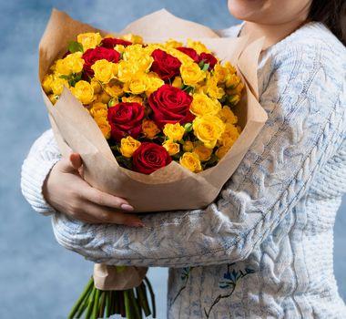Woman holding Rosa Violet Carson, Rosa Sun Flare bouquet