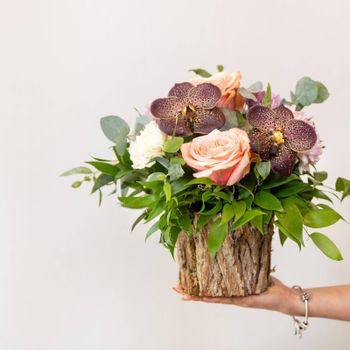 Woman holding beautiful flower bouquet in the wooden pot