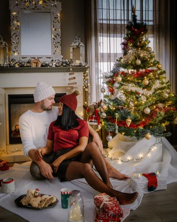 Family sitting on a floor. Couple near christmas tree, Christmas couple with present under christmas tree