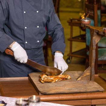 Chef cutting a chicken meat with a cleaver on the wood plate