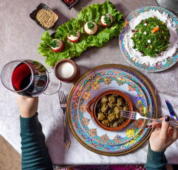 Woman eating Dolma, with red wine top view