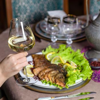 Woman eating a grilled whole fish with white wine