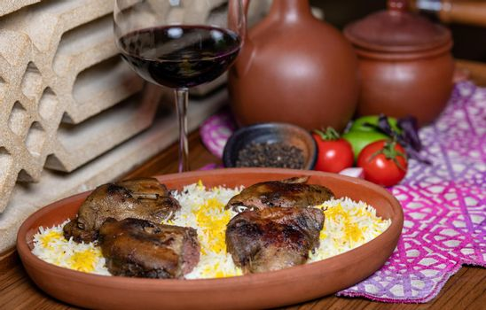 Grilled coot on the rice with red wine glass