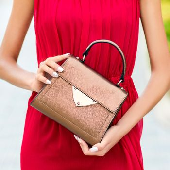 Dressed in red woman holding a luxury handbag