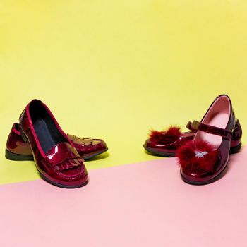 Red shiny girl shoes isolated on a colorful background