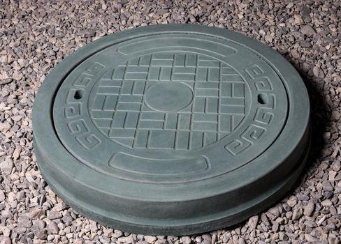 Plaster graceful stone manhole shape on the ground
