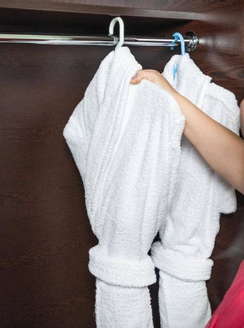 Hotel room service, woman taking out bathrobe
