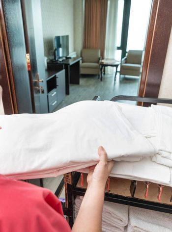 Hotel room service, woman taking a towel to the room