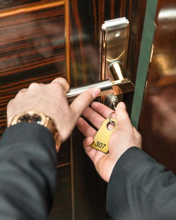 Opening the hotel room door with a key