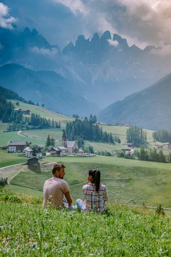 couple on vacation in the Dolomites Italy, Santa Magdalena Village in Dolomites area Italy Val di Funes
