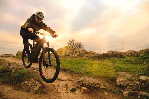 Professional Cyclist Riding Bike on the Autumn Rocky Trail at Sunset. Extreme Sport and Enduro Biking Concept.